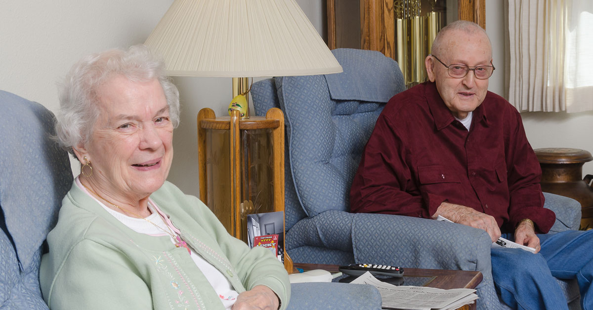 An Elderly Wife Sits At Home With Her Husband Who Is On Hospice